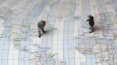 geositemaps geolocalizacion: dos indivíduos sobre un mapamundi buscan algo